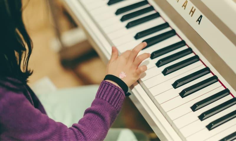 Kiedy jest ten odpowiedni czas, by zacząć naukę gry na instrumencie?, Dziecko grające na fortepianie, szkoła muzyczna