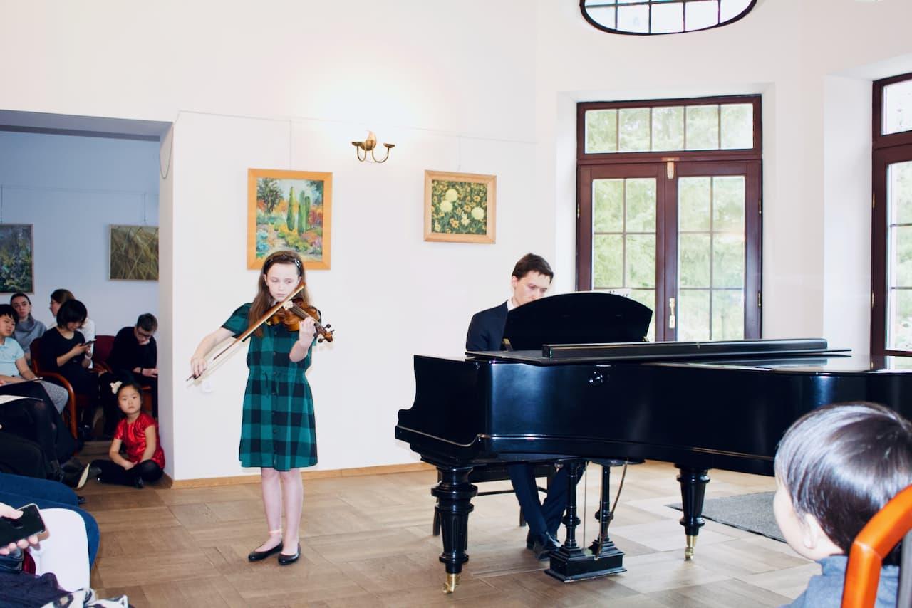zdjęcie przedstawia koncert kolędowy szkoły muzycznej z 2020 roku, gra na skrzypcach i pianinie, druga uczennica szkoły muzycznej