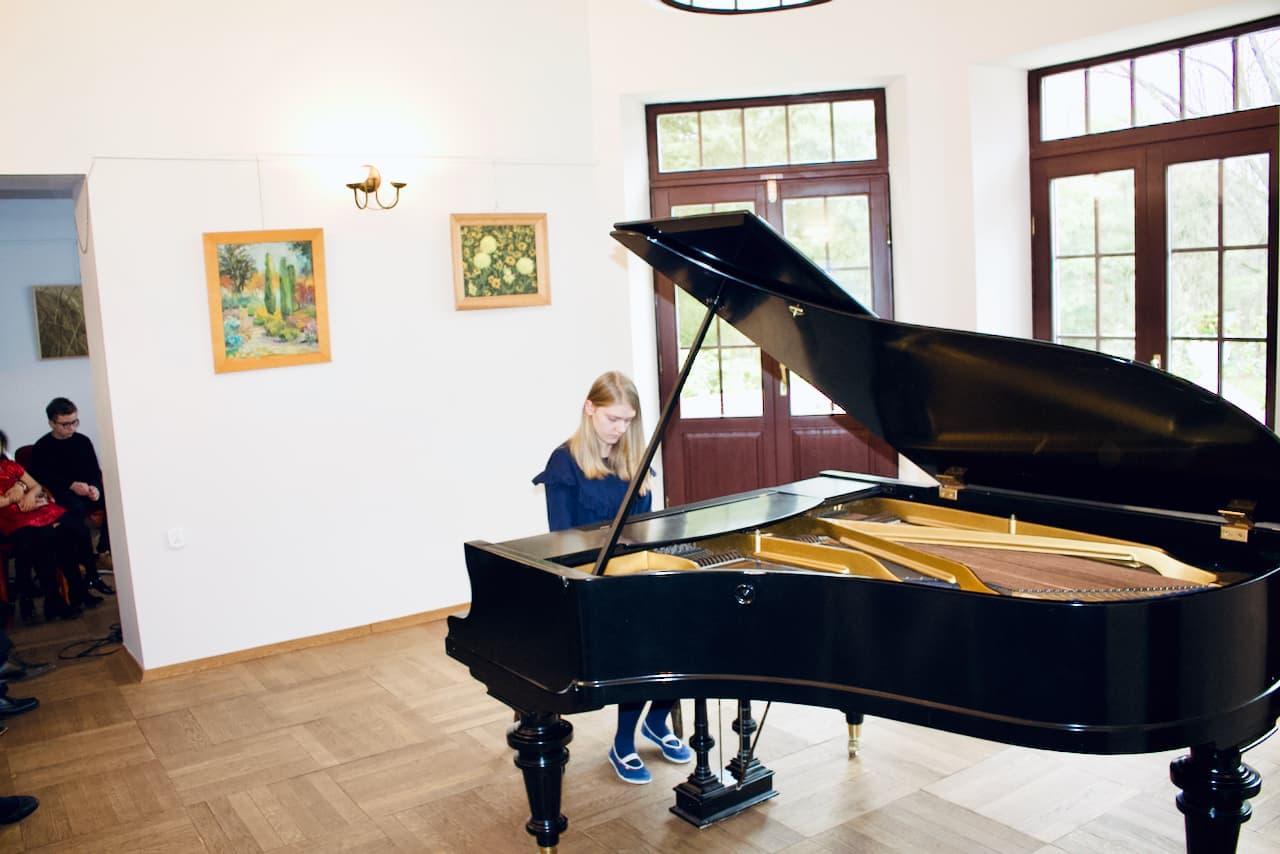 zdjęcie przedstawia koncert kolędowy szkoły muzycznej z 2020 roku, gra na pianinie, czwarty uczeń szkoły muzycznej