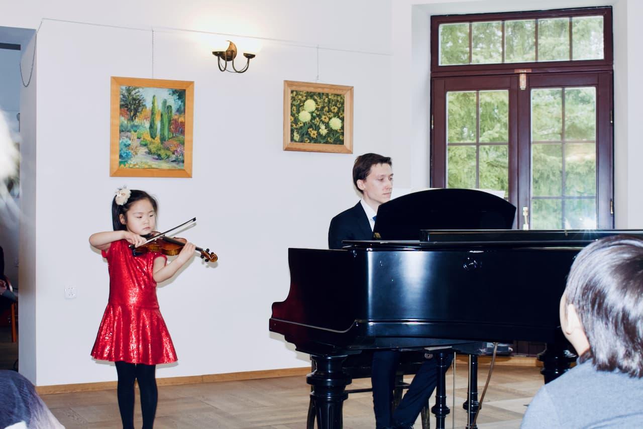 zdjęcie przedstawia koncert kolędowy szkoły muzycznej z 2020 roku, gra na skrzypcach i pianinie, akompaniament, czwarty uczeń szkoły muzycznej