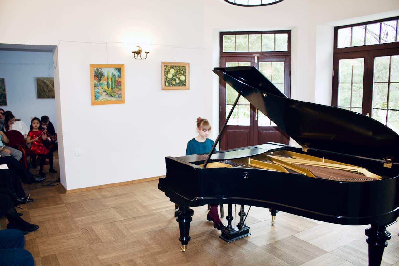 zdjęcie przedstawia koncert kolędowy szkoły muzycznej z 2020 roku, gra na pianinie, trzeci uczeń szkoły muzycznej
