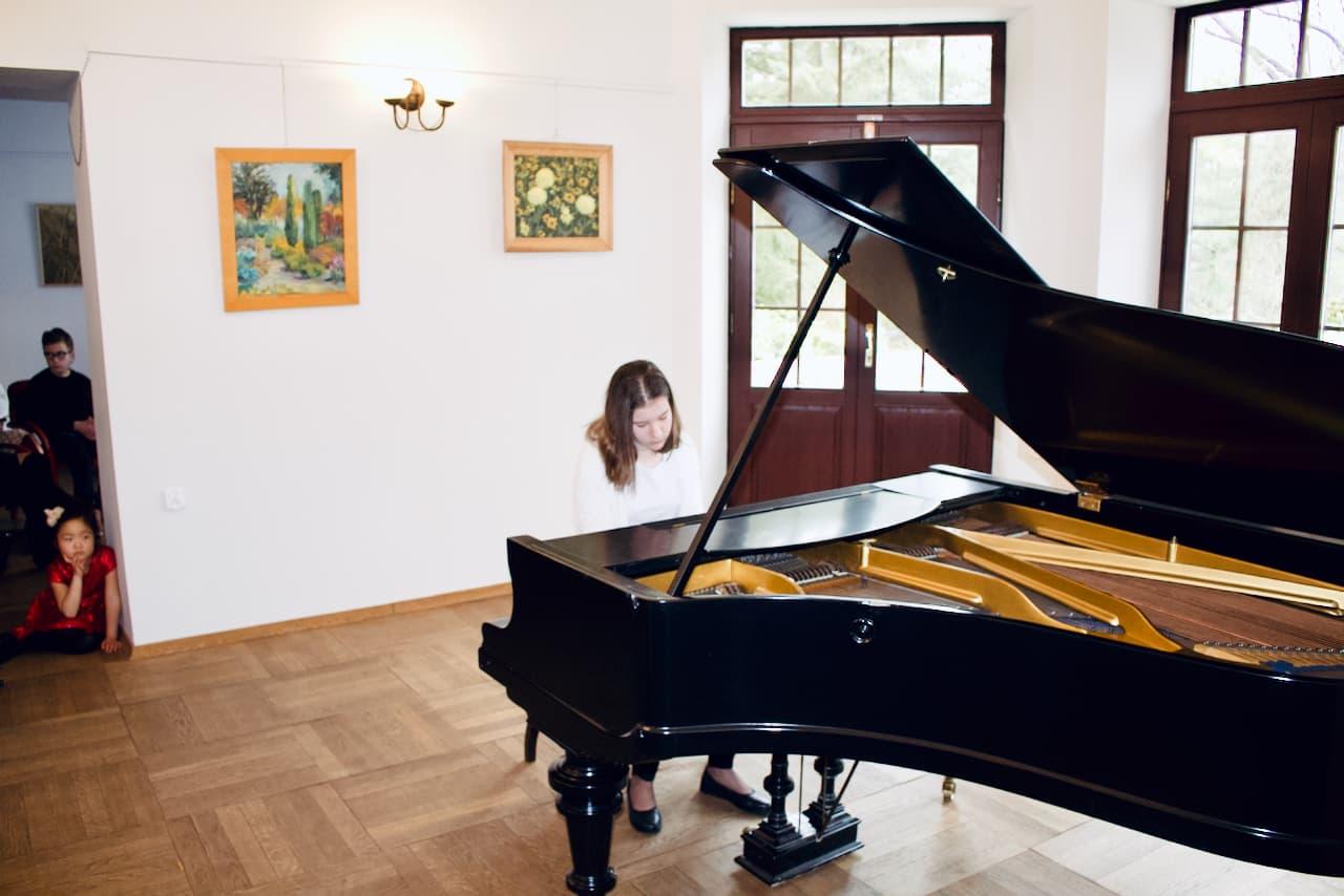 koncert kolędowy szkoły muzycznej z 2020 roku, gra 2 ucznia szkoły muzycznej unisono na fortepianie